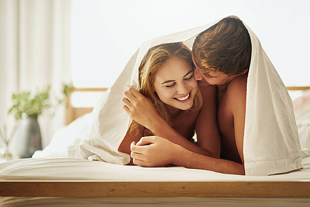 They've got a fun and fulfilling love life Shot of a young couple sharing an intimate moment under the covers in bed real couples making love stock pictures, royalty-free photos & images