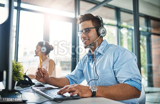Cropped shot of a handsome young man working in a call center with a female colleague in the background