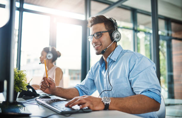 They've got the answers you're looking for Cropped shot of a handsome young man working in a call center with a female colleague in the background call centre photos stock pictures, royalty-free photos & images