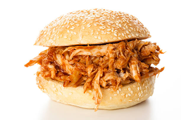 Thick amount of pulled chicken between sesame buns BBQ chicken shredded sandwich sweet bun stock pictures, royalty-free photos & images
