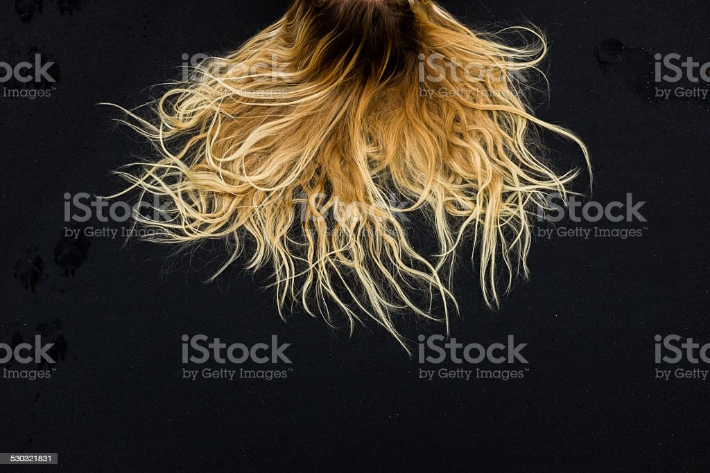 Thick blonde hair contrasted against the black sand stock photo