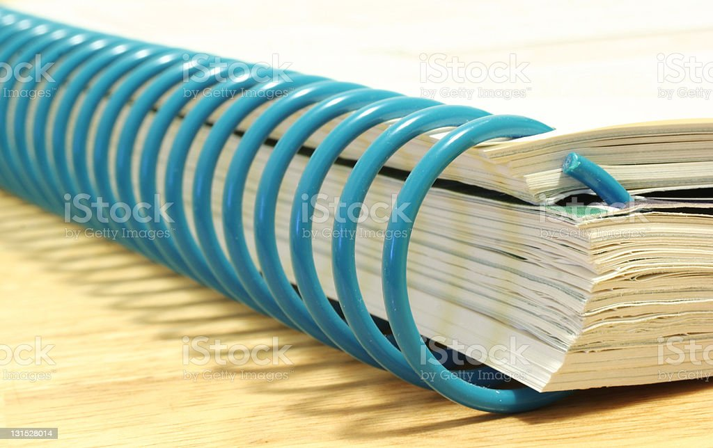 Thick book bound by blue spirals stock photo