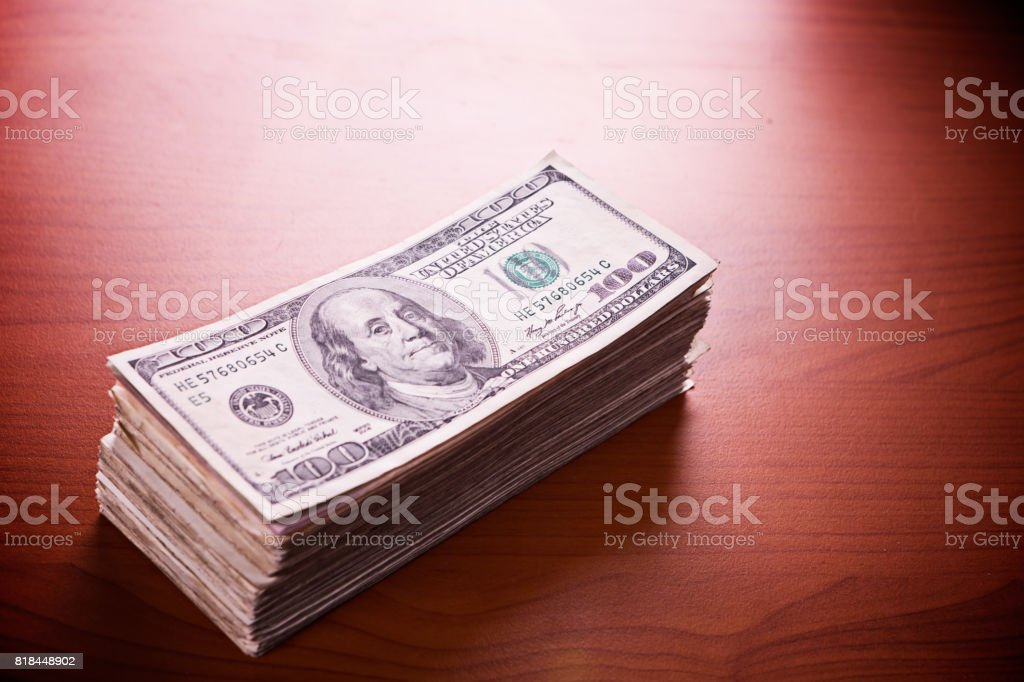 Thick bundle of American One Hundred Dollar banknotes on wood stock photo