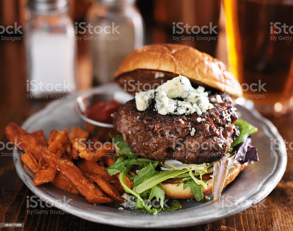 thick burger with blue cheese and sweet potato fries stock photo
