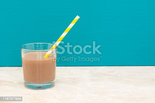 Thick chocolate milkshake with a retro paper straw in a glass tumbler with a teal background and copy space