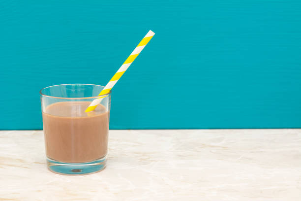 Thick chocolate milkshake with a straw in a glass Thick chocolate milkshake with a retro paper straw in a glass tumbler with a teal background and copy space chocolate milk stock pictures, royalty-free photos & images