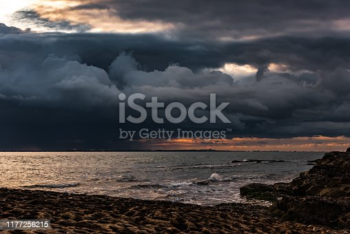 Thick dark thunderclouds above the sea