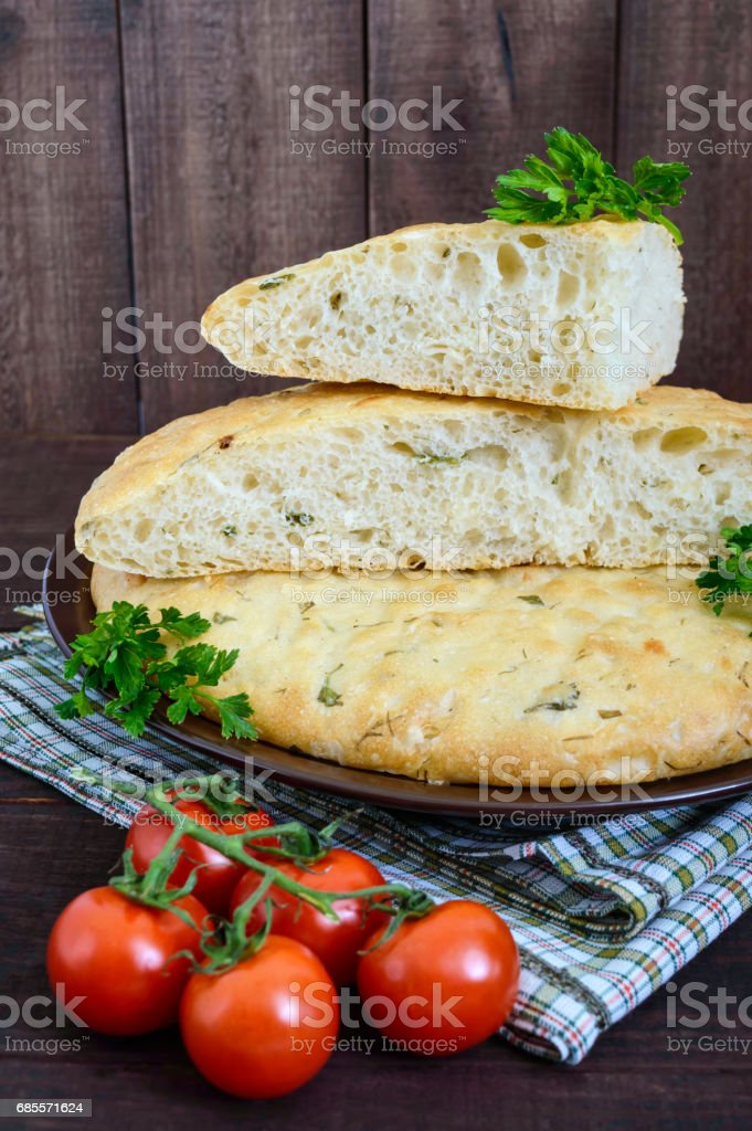 A thick flat cake - pita bread with greens on a dark wooden background. A traditional Asian dish. royalty-free 스톡 사진