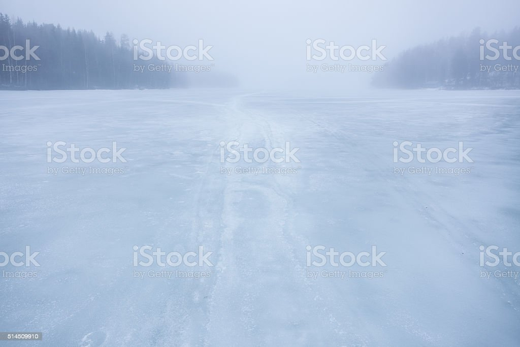 Thick fog at frozen lake landscape stock photo