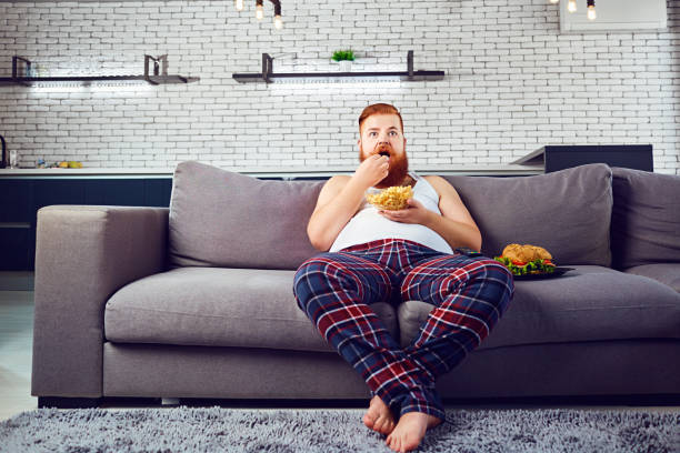 thick funny man in pajamas eating a burger sitting on the couch - stomach sitting stock photos and pictures