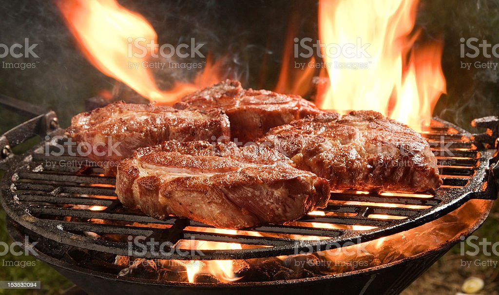 Thick pork steaks on a grill, flames royalty-free stock photo