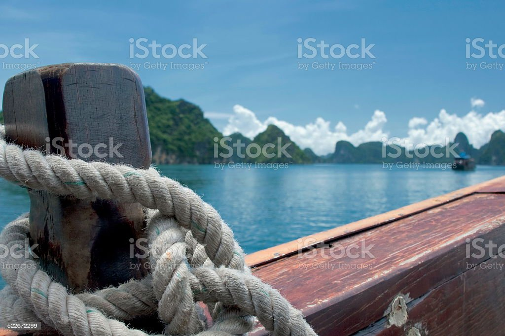 thick rope tied to a wooden stern in sea ship stock photo