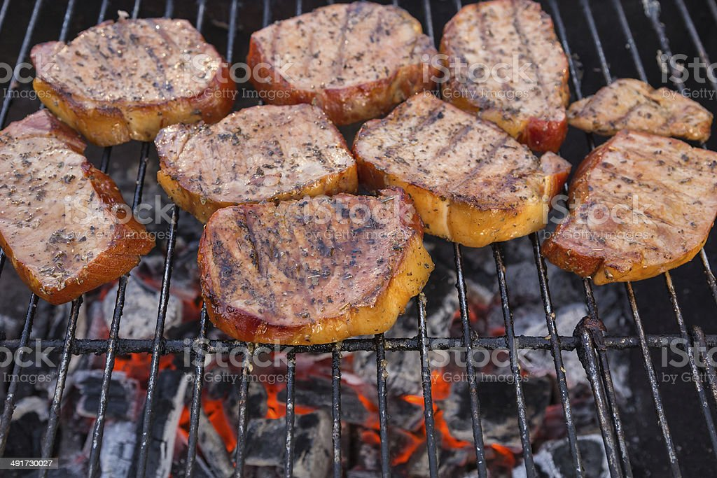 Thick seasoned pork chops cooking on the grill stock photo