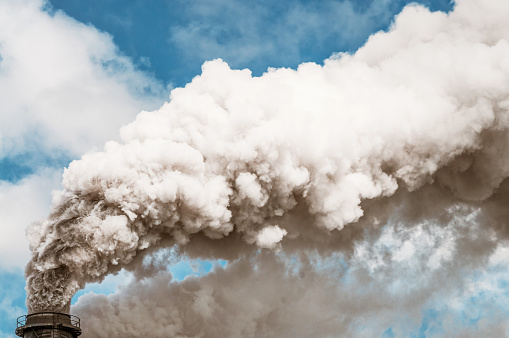 Air pollution: Thick smoke billowing into the sky from a factory chimney.
