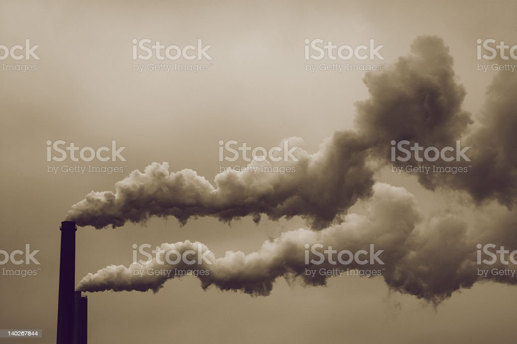 Thick strong black smoke coming from chimneys stock photo