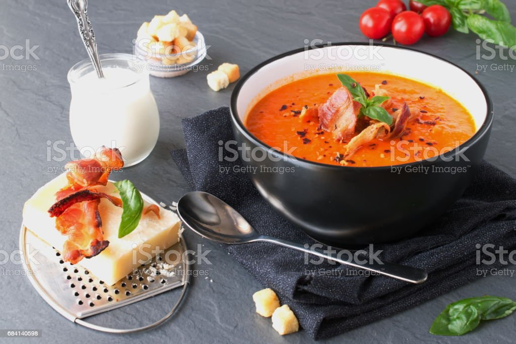 Thick tomato soup with basil and fried bacon in a black ceramic bowl on a grey abstract background. Healthy eating concept foto de stock libre de derechos