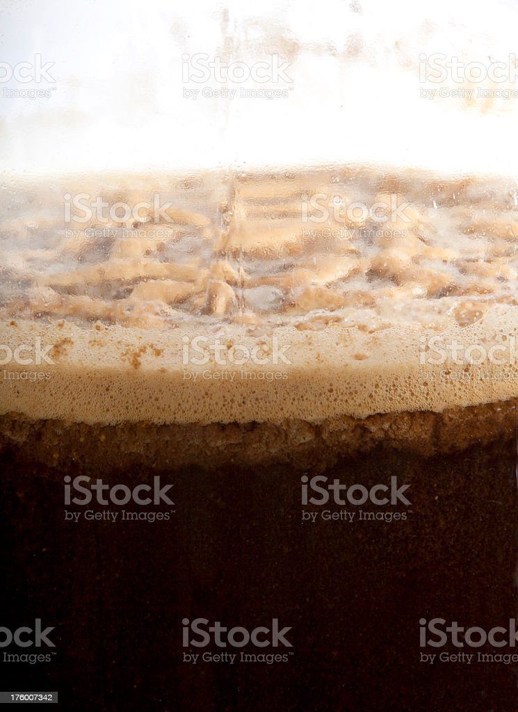 Thick yeast froth atop a carboy full of brewing beer stock photo