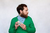 istock Thief - Bearded man hiding a bundle of money 942226784