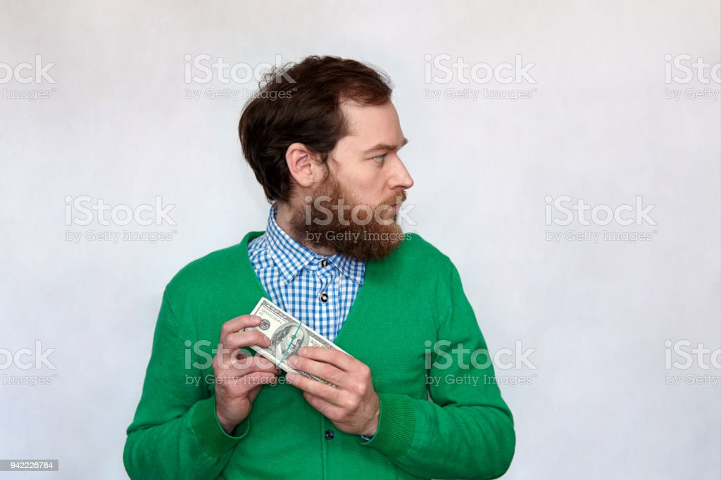 Thief - Bearded man hiding a bundle of money stock photo