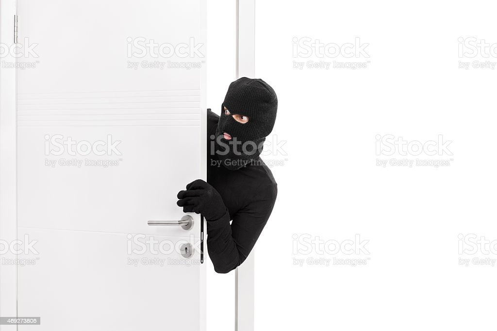 Thief breaking into a room and carefully looking around stock photo
