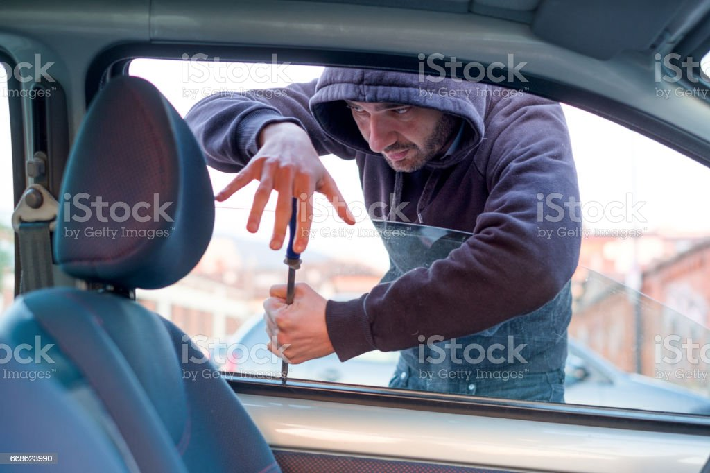 Thief breaking the car window to steal one car stock photo