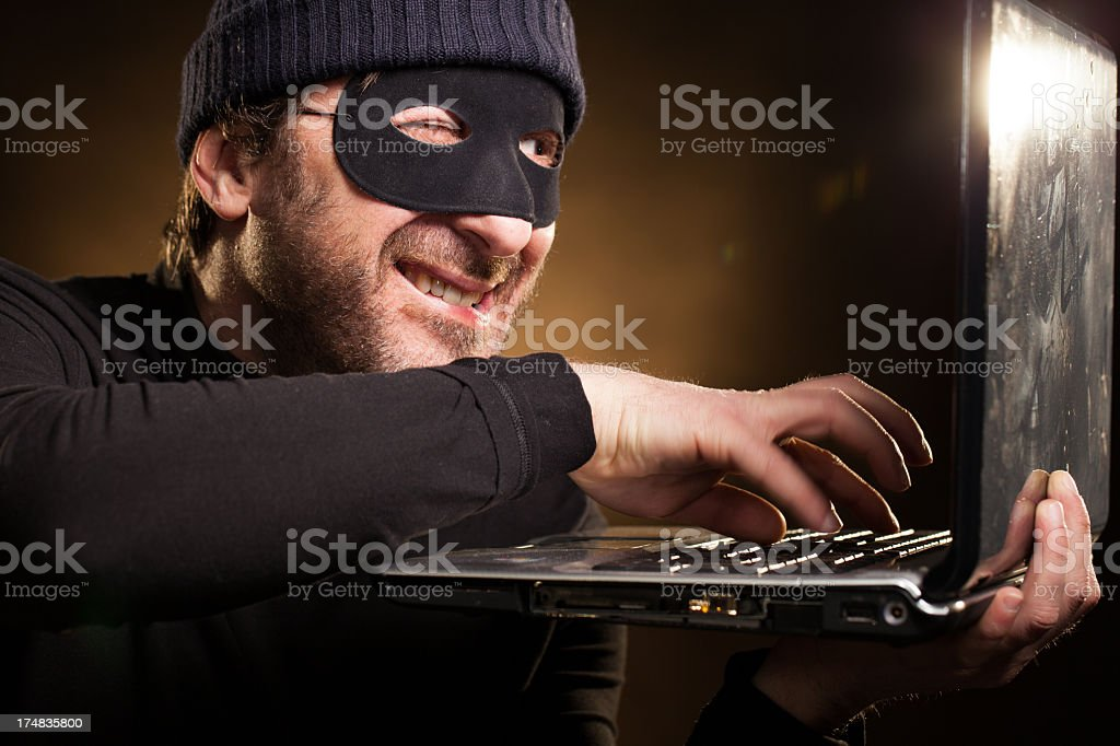 Thief Cunningly Stealing Data on a Laptop Computer stock photo