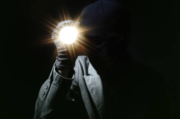 Thief holding a torch in dark stock photo