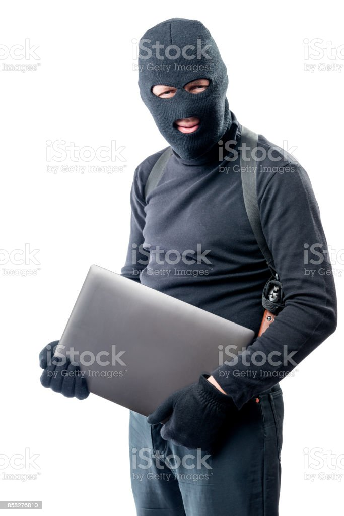 Thief in a balaclava with a laptop on a white background stock photo