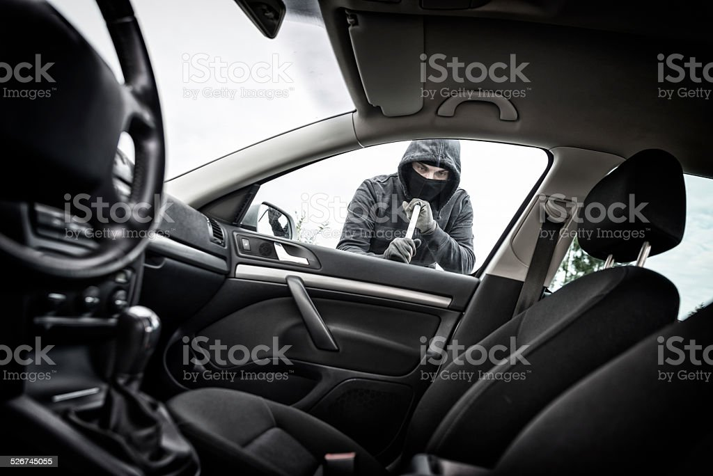 Thief in a mask hijacks the car stock photo