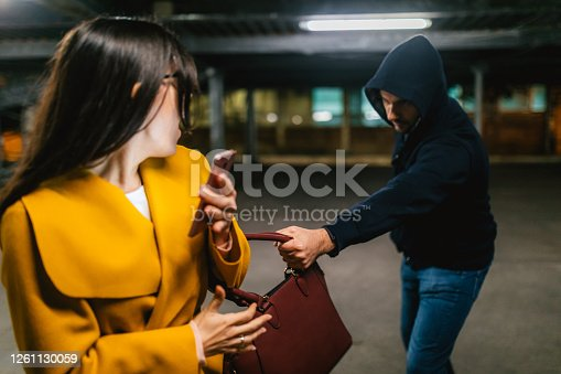 Two people, man and woman, criminal in action, purse robbery, cropped.