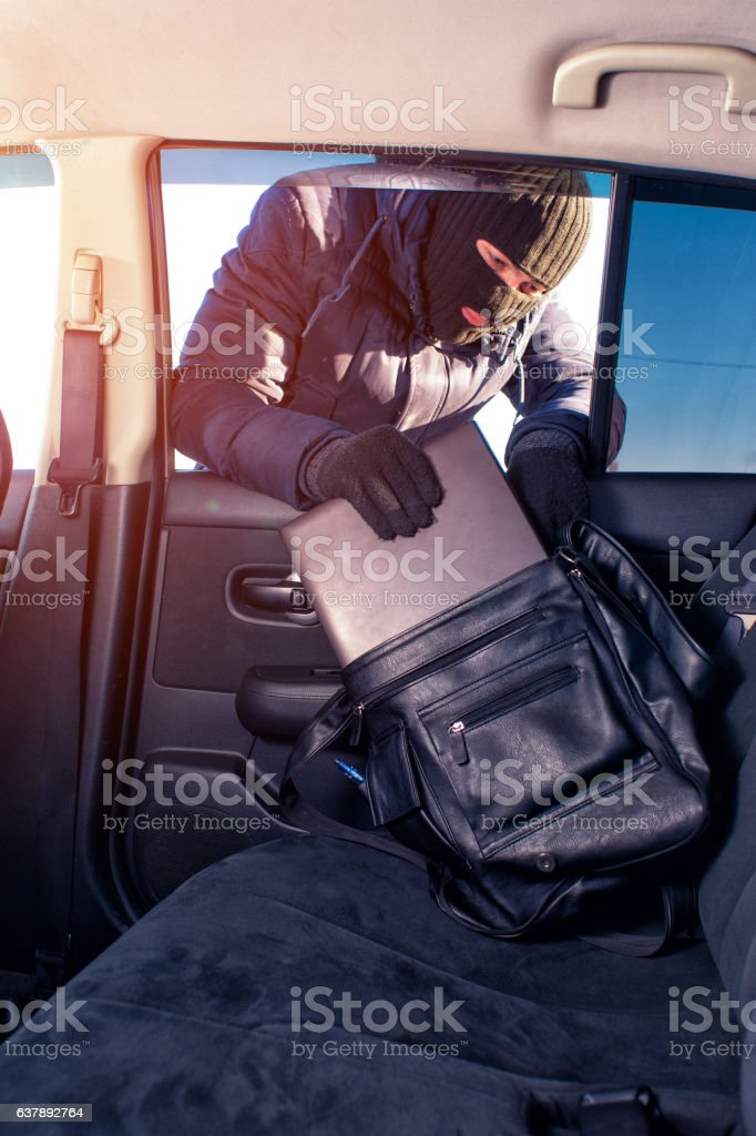 Thief in robbery mask stealing laptop from car ストックフォト