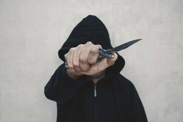 Thief in the hood on a black background Thief in the black hood. black silhouette of guy. Anonymous. The threat of life. A criminal element. cutthroat stock pictures, royalty-free photos & images