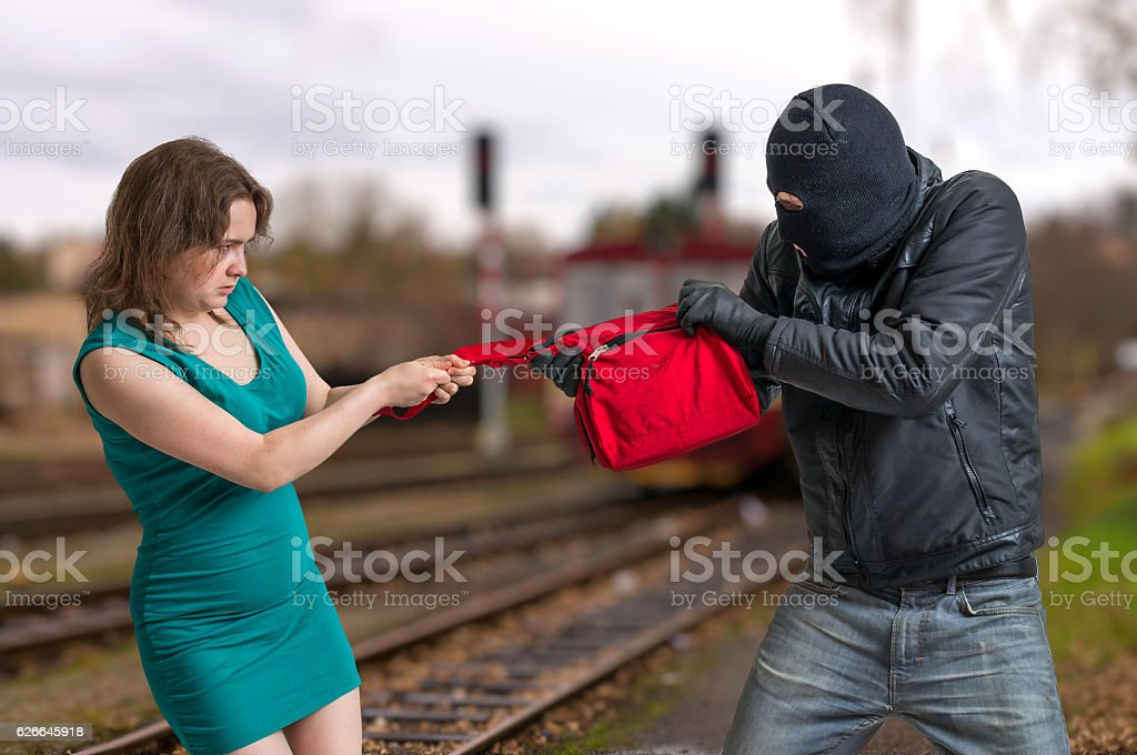 Thief is fighting with woman and stealing handbag. stock photo
