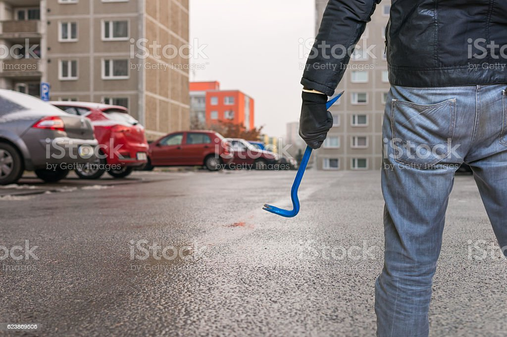 Thief is going to steal car from parking lot. stock photo