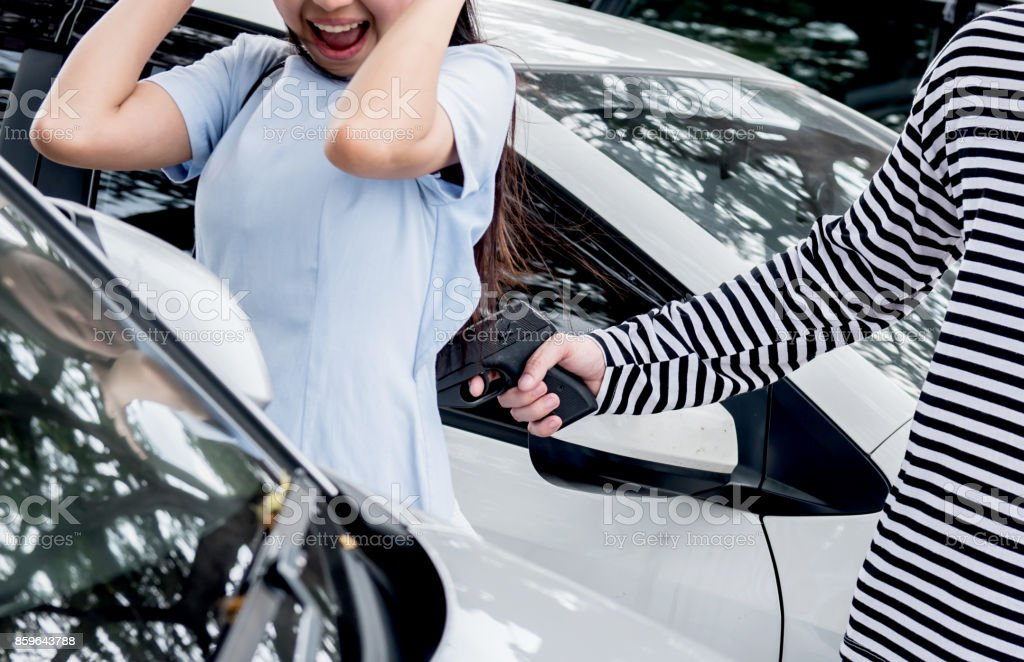 Thief is trying to steal the car at the public parking stock photo