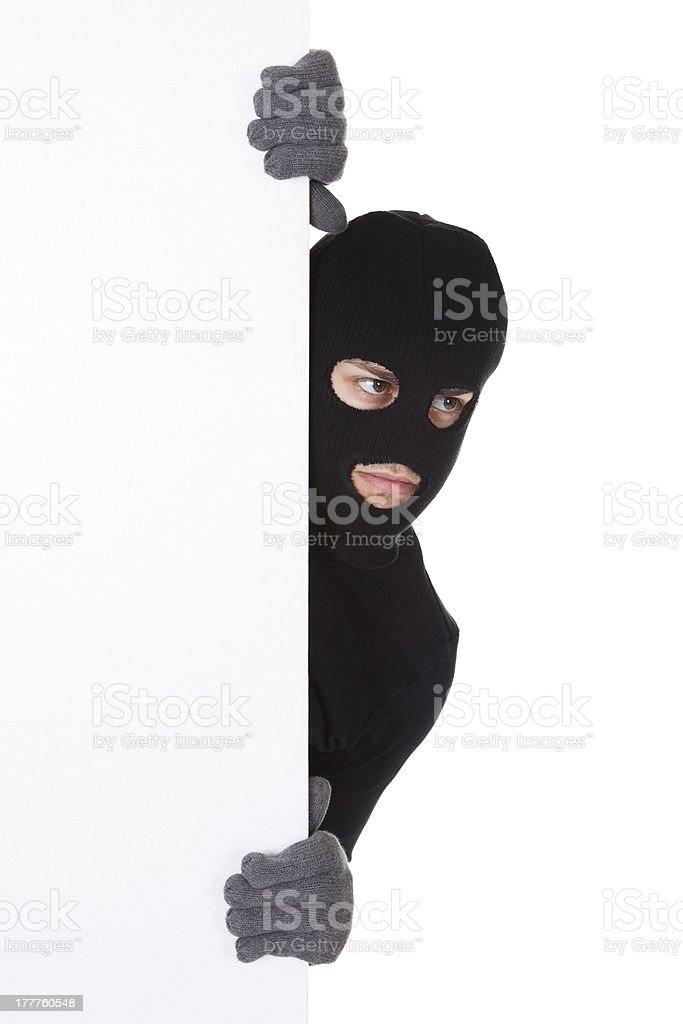Thief looking around a blank sign royalty-free stock photo