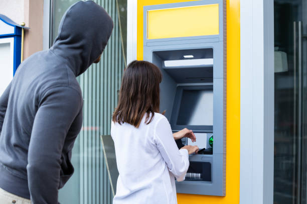 Thief Looking At Woman Entering The Pin In ATM Male Trying To Steal Pin Code Of Woman's Card Using ATM For Withdrawing Cash identity theft stock pictures, royalty-free photos & images