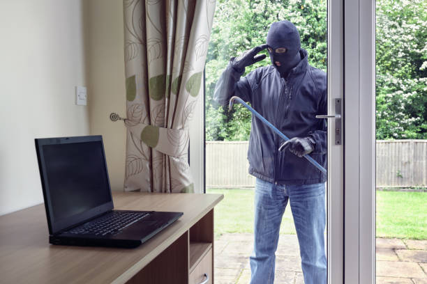 Thief looking through patio doors window at a laptop computer to steal stock photo