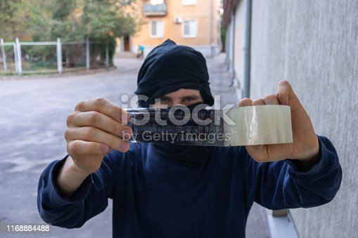 istock thief man in mask taping the cctv camera outside to break in the house 1168884488