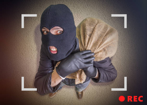 Thief or robber with bag full of money is being recorded with camera at night. View from top. stock photo
