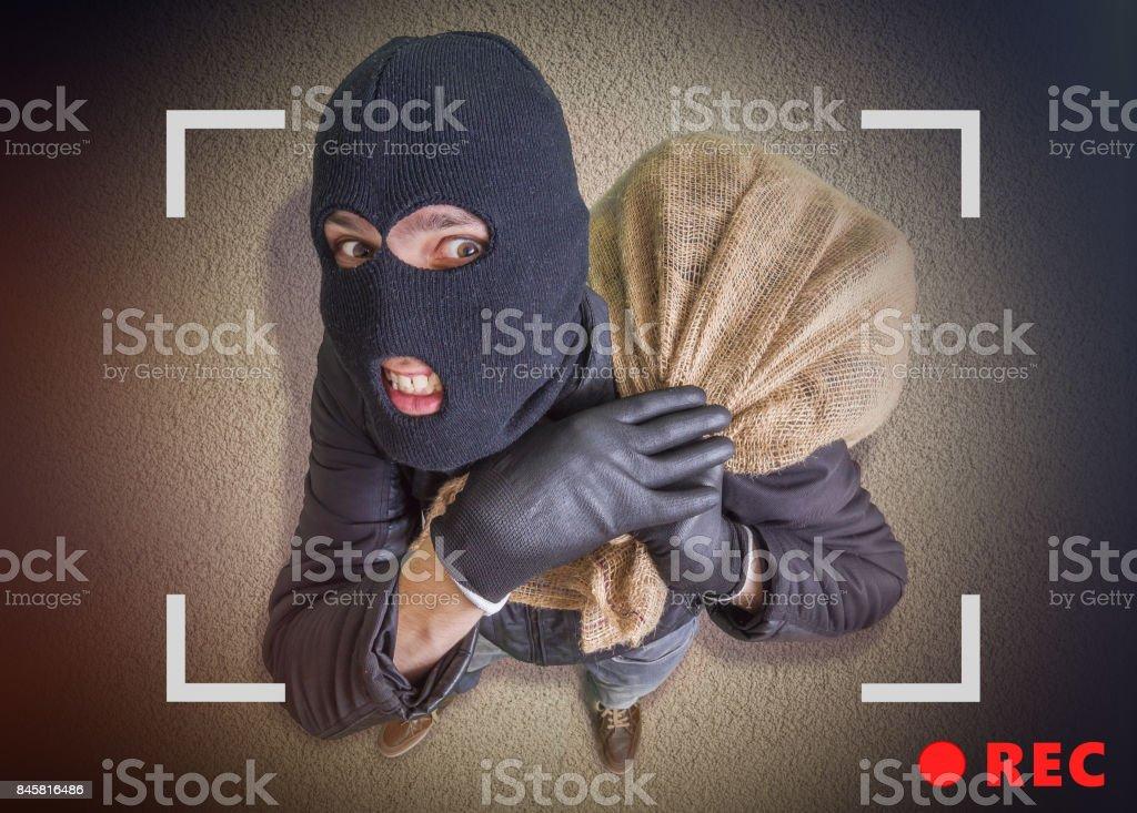 Ladrão ou assaltante com saco cheio de dinheiro está sendo gravado com câmera à noite. Vista de cima. - foto de acervo