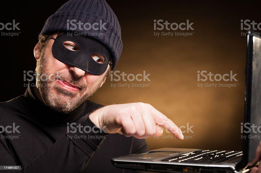 Thief Pressing the Enter Button on a Laptop Computer stock photo