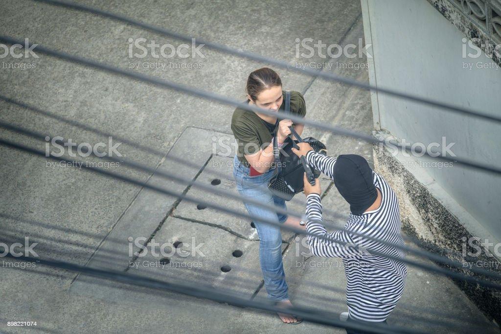 Dieb Diebstahl Frau mit Waffe, gefährlicher Verbrecher der Frauen in der Stadt. Eine Frau ist so verängstigt. Dieb in Balaclava mit Holding-Pistole, Outlaw schlechter Mensch halten eine Waffe auf das Ziel – Foto