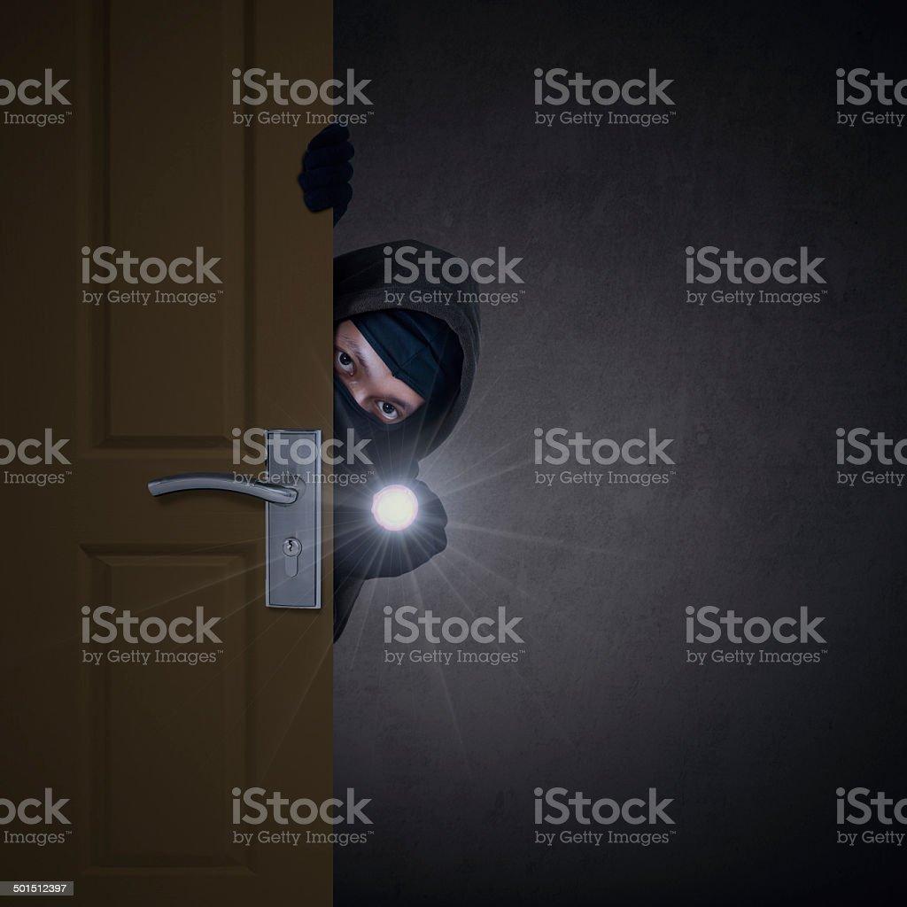 Thief sneaking through door stock photo