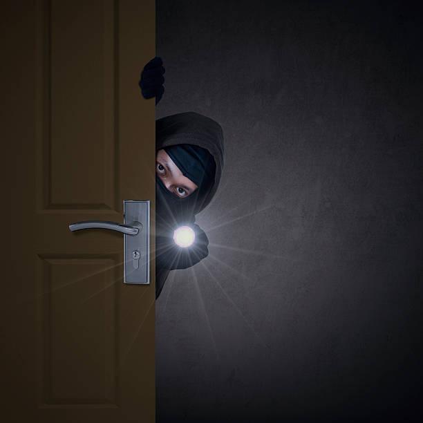 Thief sneaking through door