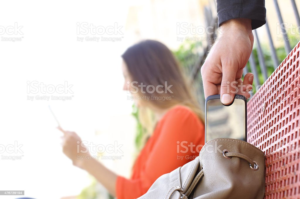Thief stealing a mobile phone stock photo