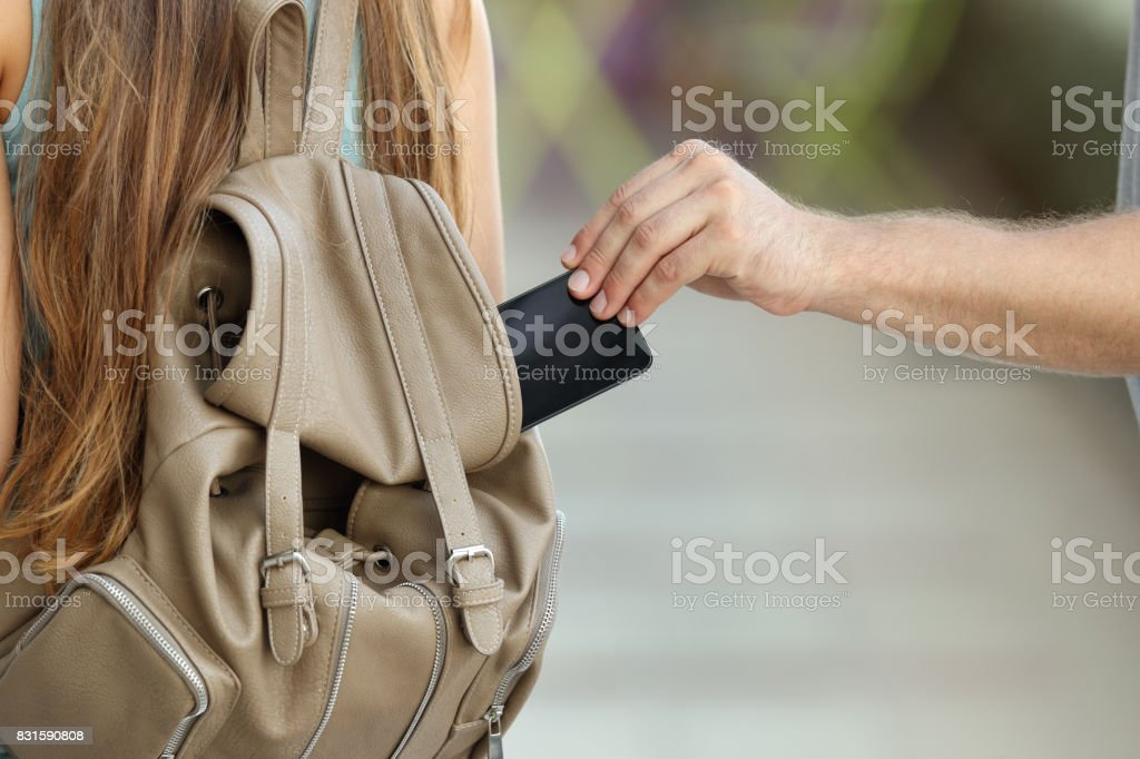 Thief stealing a phone from a bag stock photo