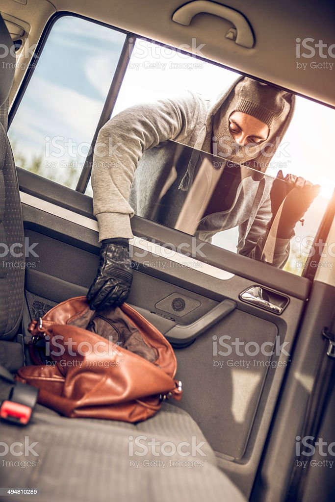 Thief stealing a purse from the car stock photo
