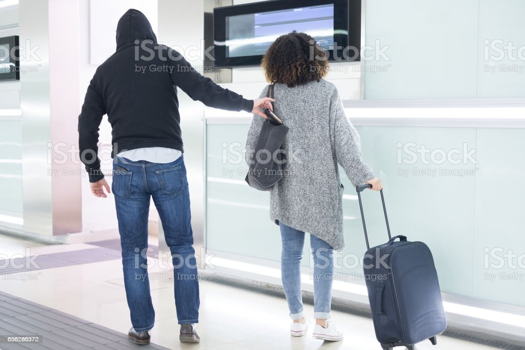 Thief stealing a wallet from a bag stock photo