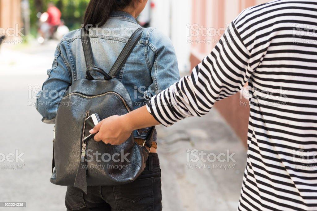 ladrón de robar el teléfono inteligente de mochila de viajero mujer - Foto de stock de Adulto libre de derechos